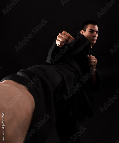 Photo  Studio portrait of young karate fighter kicking over black background