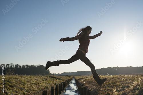 小川を飛び越える女性 Poster