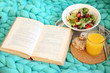 Leinwanddruck Bild - Open book, plaid and juice on sofa