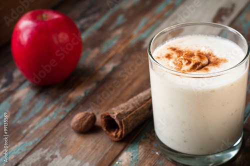 Spoed Foto op Canvas Milkshake Apple crumble smoothie milkshake topped with cinnamon and nutmeg spices. Served on a rustic wooden table.