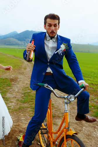 Fotografija  drunken groom on a bike holding a beer bottle.