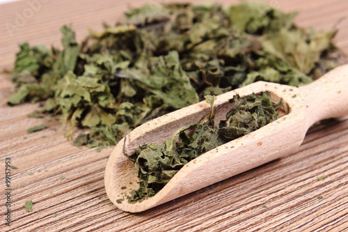 fototapeta na szkło Dried nettle with spoon on wooden surface
