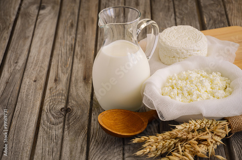 Poster Produit laitier Fresh dairy products. Milk and cottage cheese with wheat on the rustic wooden background. Horizontal permission. Selective focus.