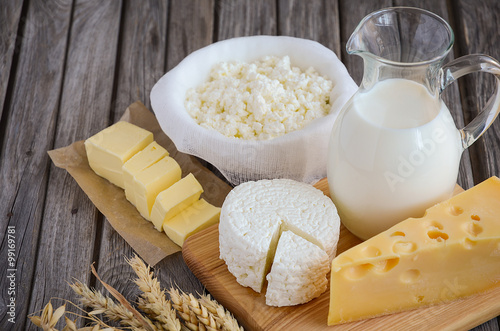 Poster Dairy products Fresh dairy products. Milk, cheese, butter and cottage cheese with wheat on the rustic wooden background. Horizontal permission. Selective focus.