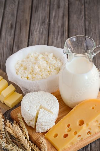 Staande foto Zuivelproducten Fresh dairy products. Milk, cheese, butter and cottage cheese with wheat on the rustic wooden background. Selective focus.