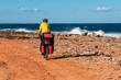 man goes sandy beach on mountain bike with big backpack.