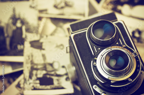 Old camera is lying on vintage family photos