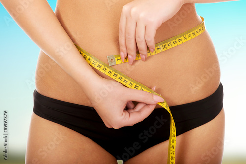 Fotografia  Woman measuring her waist.