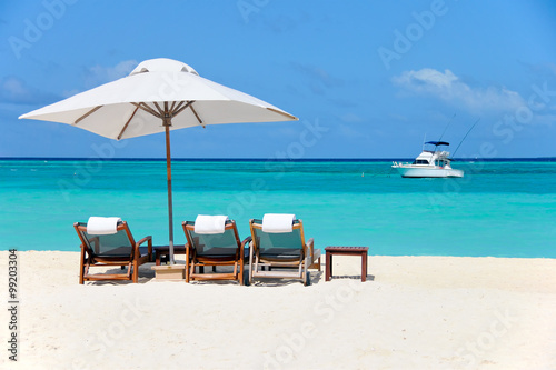 Staande foto Strand three beach chairs with white umbrella and yacht at ocean front