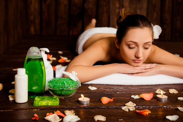 Obraz na płótnie Canvas Calm pretty young woman laying in spa salon with closed eyes and
