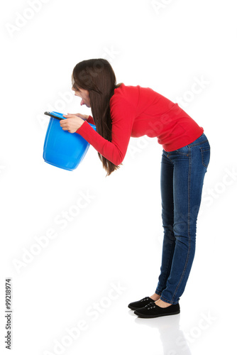 Fotografia  Young woman vomiting to bucket.