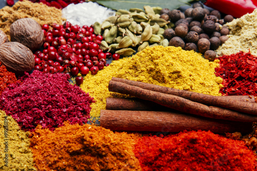 assortment of spices seasoning on a black stone - 99250194
