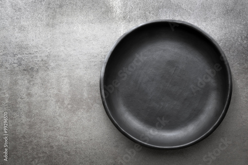Foto  Empty Rustic Black Plate over Slate