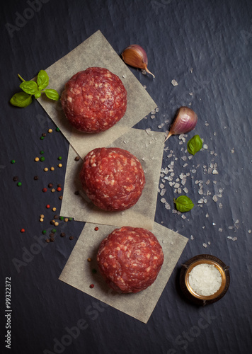Raw ground beef meat steak cutlets with herbs and spices on blac Fotobehang