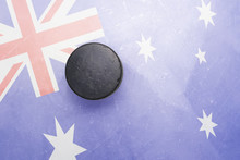 Old Hockey Puck Is On The Ice With Australia Flag