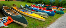 Canoes And Kayaks / Group Of Canoes And Kayaks On A Green Grass