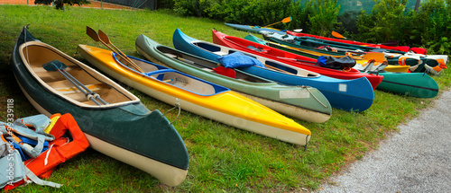 Leinwand Poster Canoes and Kayaks / Group of canoes and kayaks on a green grass