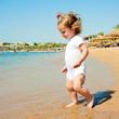 Cute baby girl having fun on beach.