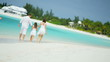 Caucasian family parents girl white clothes beach ocean island vacation tourism