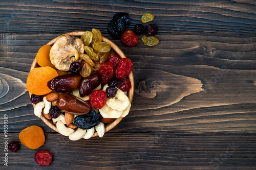 Photo Mix of dried fruits and nuts on a dark wood background with copy space