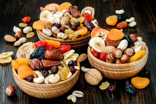 Photo Mix of dried fruits and nuts on dark wood background