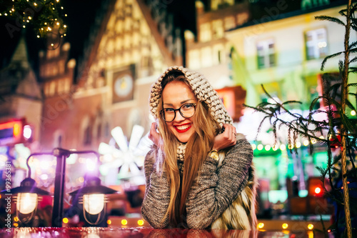 Fototapety, obrazy: Street portrait of smiling beautiful young woman with glasses and scarf on head on the festive Christmas fair. Model smile at camera.  Christmas market