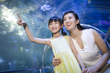 Young Mother And Daughter In Aquarium