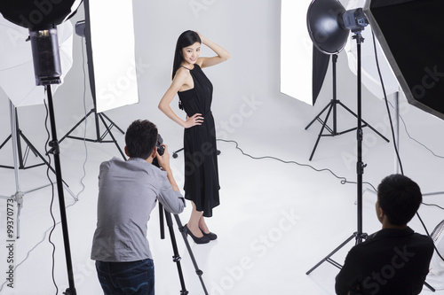 Photographers Taking Pictures Of Female Model In Studio