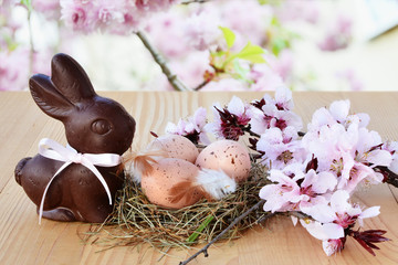 Naklejka Easter background, card with easter eggs, chocolate bunny and pink spring blossoms