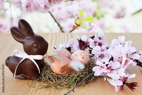 Easter background, card with easter eggs, chocolate bunny and pink spring blossoms - 99374712