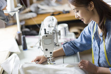 Side View Of Fashion Designer Working On Sewing Machine