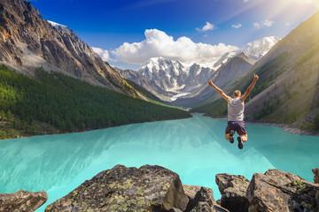 Prekrasan planinski krajolik s jezerom i čovjekom koji skače. Koncept ekstremnih sportova.