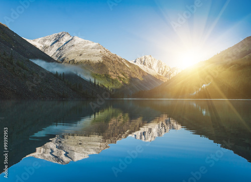 Spoed Fotobehang Reflectie Sunrise and mountains reflected in the water