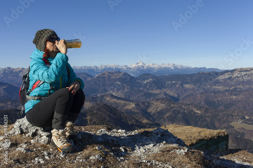 Pretty mid aged woman trekker with backpack drinks high in mountains on  sunny winter day. abdfb976efc90