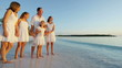 Young Caucasian parents and daughters on beach at sunrise