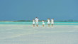 Caucasian family wearing white clothes barefoot on a beach