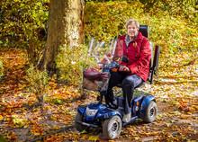 Seniorin Mit Elektromobil Im Herbstwald