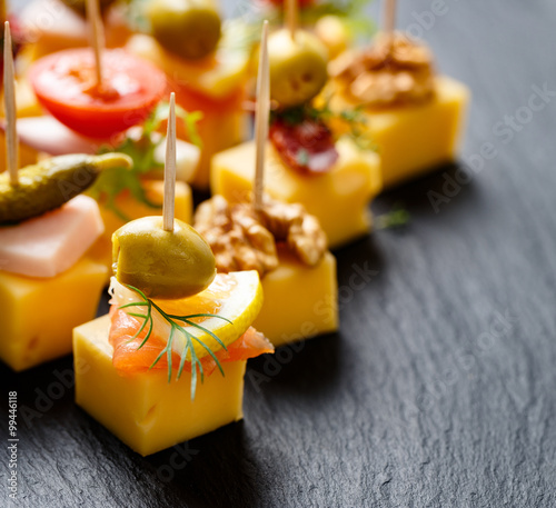 Poster de jardin Entree Various cheese skewers on a black background