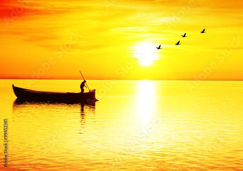 Spoed Foto op Canvas Geel atardecer en el mar y un pescador en su barco