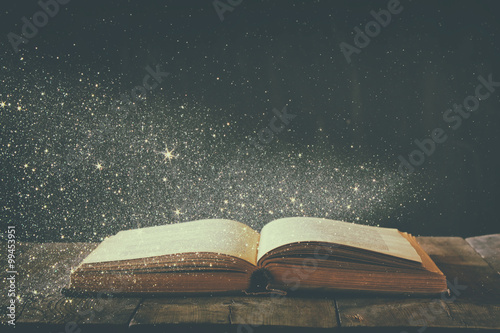 abstract image of open antique book on wooden table Poster