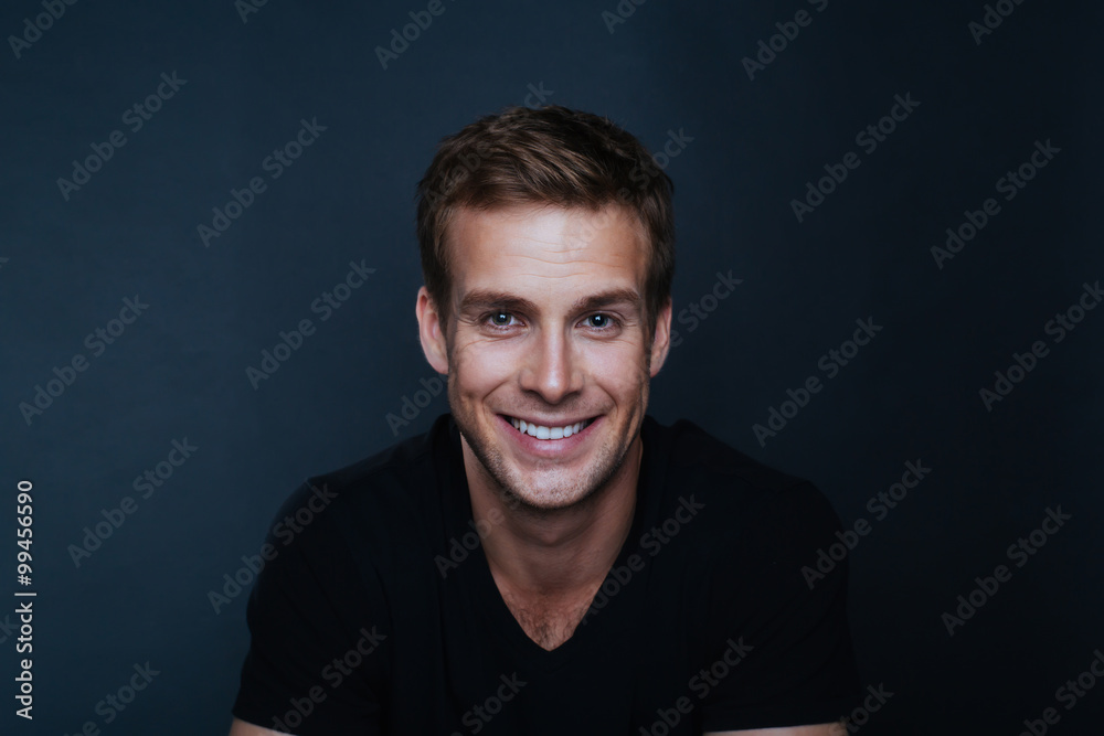 Fototapeta Portrait photo of young happy man with a blinding smile in v nec