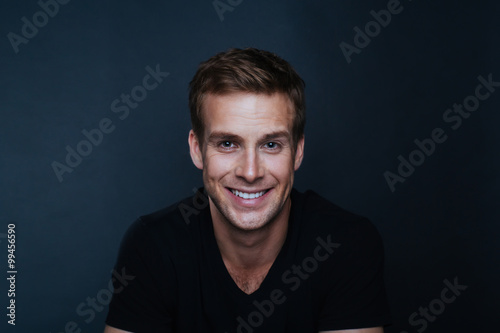 Portrait photo of young happy man with a blinding smile in v nec Tablou Canvas
