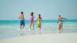 Caucasian family wearing colorful swimwear barefoot on beach