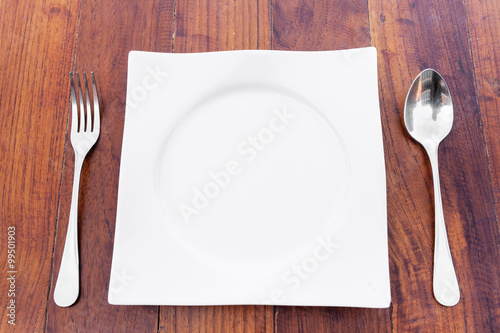 white plate Spoon and fork on a brown wooden table