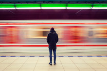 Long Exposure Of Lonely Man At Subway Station With Blurry Moving Train