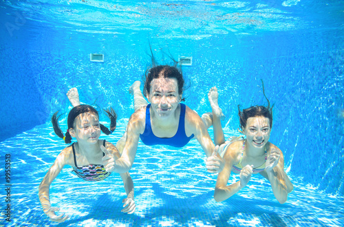 Family swim in pool underwater, happy active mother and children have fun under Canvas Print