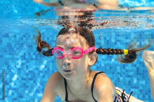 Plakat Dziecko pływa w basenie pod wodą, szczęśliwa aktywna dziewczyna w gogle ma zabawy pod wodą, sport dzieci