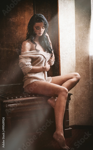 Fototapeta Attractive sexy brunette half naked posing provocatively in window frame. Portrait of sensual woman in classic boudoir scene. Woman with long hair daydreaming and enjoying the bright day light obraz na płótnie