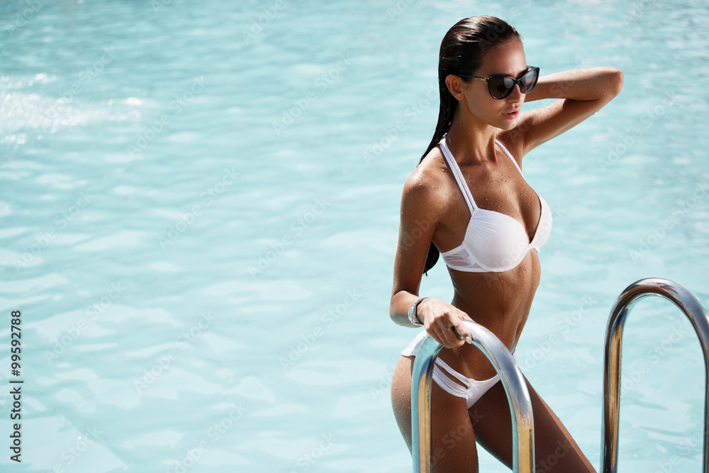 Fototapety, obrazy: Elegant sexy woman in the white bikini on the sun-tanned slim and shapely body is posing near the swimming pool