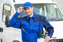 Confident Pest Control Worker Wearing Cap Against Truck